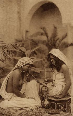 Harem girls smoking a hookah, from an early 20th century postcard (sepia photo)