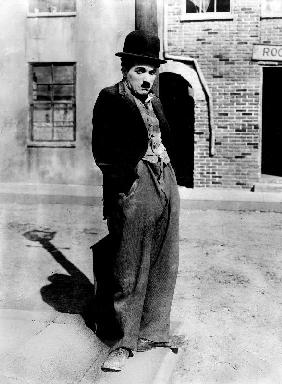 A dog 's life by and with Charlie Chaplin , standing in a street, hands in pockets. Los Angeles