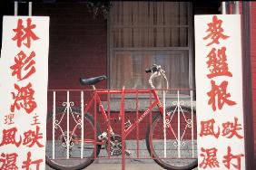 Bicycle at metal bars with Chinese board , Singapore (photo)