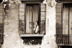 Woman gazing out of a window contemplating, 2004 (b/w photo)