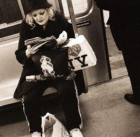 Woman reading on a subway with a Marilyn Monroe purse and an ''I Love New York'' bag, 2004 (b/w phot